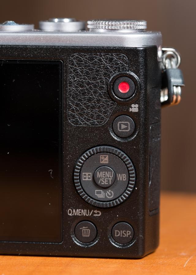 GM1:n takaa löytyy videokuvauksen käynnistys (punainen ympyrä, kuvien katselu, valintakiekko/ympyrä sekä pikavalikko ja display -painikkeet. Valintakiekko/ympyrä on kaksitoiminen, mikä aiheuttaa pienen kokonsa takia monissa tilanteissa helposti virhepainalluksia